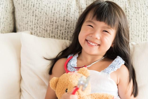 Nettes kleines mädchen lächelt und spielt doktor mit stethoskop und teddybären.