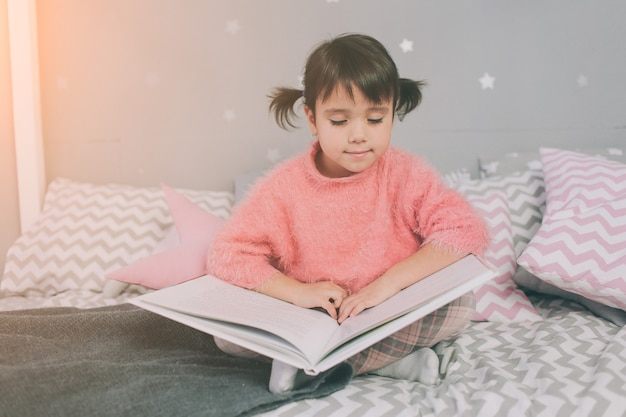 Nettes kleines mädchen liest zu hause ein buch. lustiges schönes kind, das spaß im kinderzimmer hat