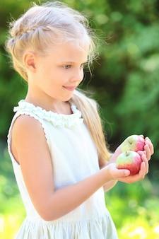 Nettes kleines mädchen mit äpfeln im freien
