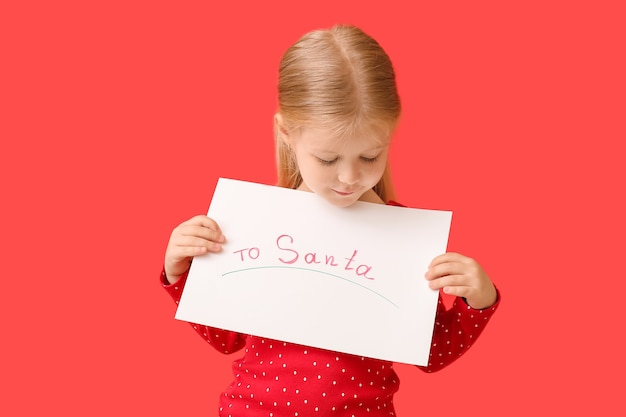 Nettes kleines mädchen mit brief an den weihnachtsmann auf farboberfläche