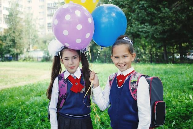 Nettes kleines mädchen mit bunten ballons in der nähe der schule an der schuluniform