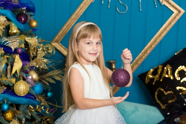 Nettes kleines mädchen mit dem langen haar weihnachtsbaum verzierend.