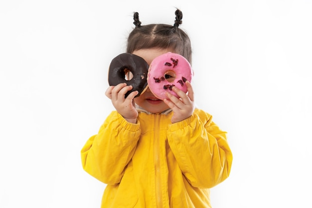 Nettes kleines mädchen mit donuts auf einem weißen hintergrund