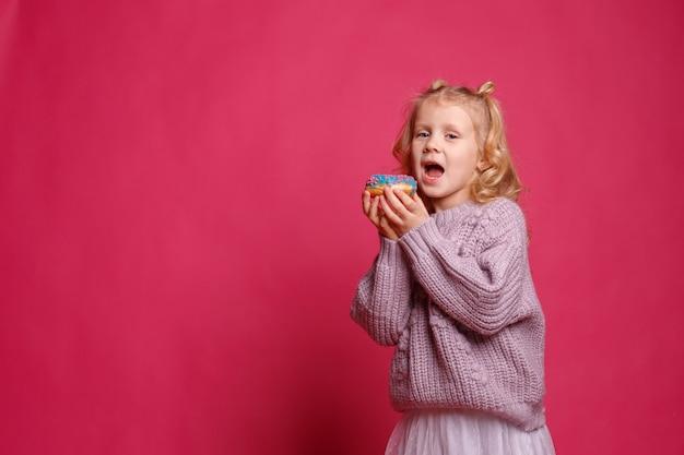 Nettes kleines mädchen mit einem donut auf einem rosa hintergrund. das kind gibt sich mit essen hin. spaß mit donuts