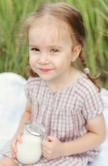 Nettes kleines mädchen mit einem krug milch auf dem feld an einem sommertag, glückliche kindheit.