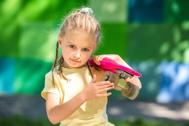 Nettes kleines mädchen mit einem skateboard auf ihrer schulter