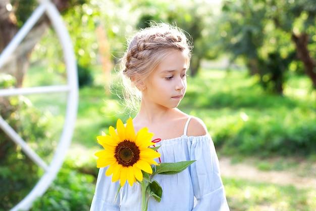 Nettes kleines mädchen mit einem zopf auf dem kopf hält eine sonnenblume im sommergarten.
