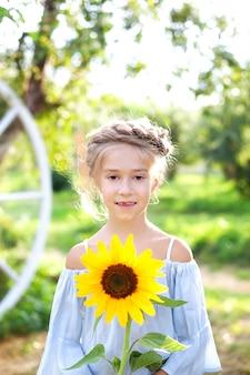 Nettes kleines mädchen mit einem zopf auf dem kopf hält eine sonnenblume. kindheitskonzept. ein kind mit einer sonnenblume im garten. naturkonzept, spaß. kleines mädchen, das natur an einem sonnigen sommertag genießt.