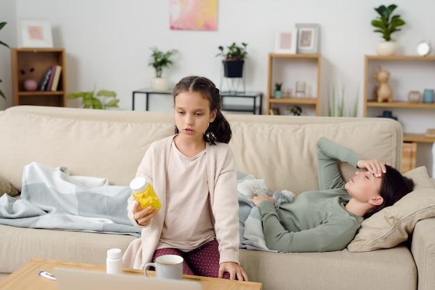 Nettes kleines mädchen mit einer flasche pillen, die es dem online-arzt zeigt und die symptome ihrer kranken mutter beschreibt, während sie vor dem laptop sitzt