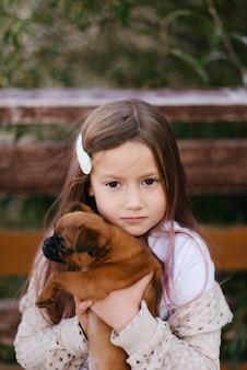 Nettes kleines mädchen mit einer haarnadel im haar, die einen hund hält
