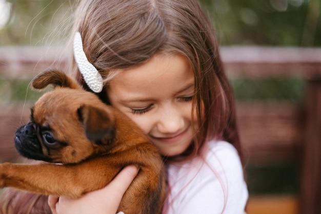 Nettes kleines mädchen mit einer haarnadel im haar umarmt einen braunen hund