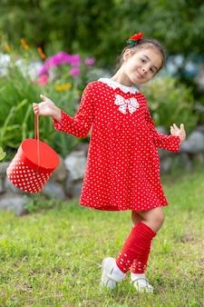 Nettes kleines mädchen mit einer roten tasche und kleid mit tupfen
