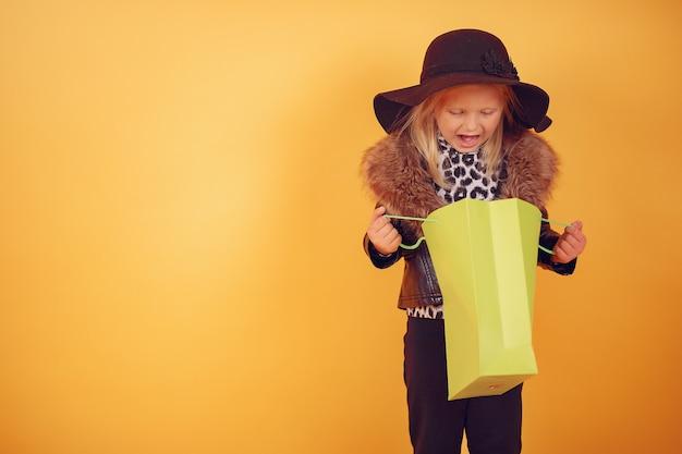 Nettes kleines mädchen mit einkaufstaschen auf einem gelben hintergrund