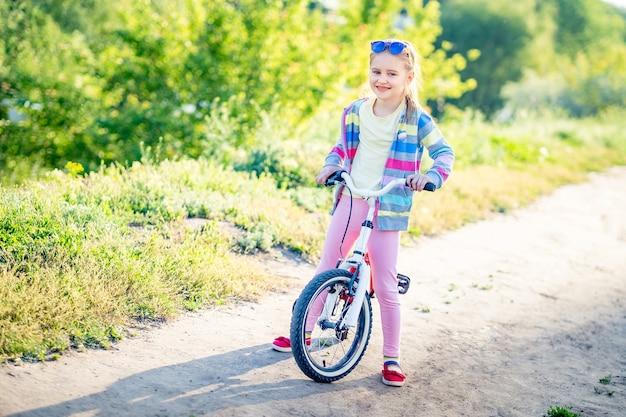Nettes kleines mädchen mit ihrem fahrrad auf dem weg