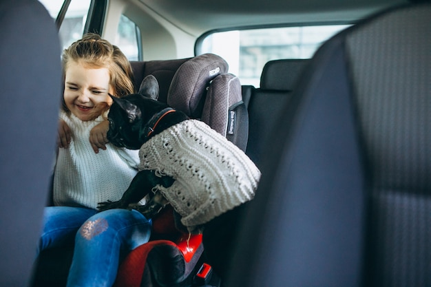 Nettes kleines mädchen mit ihrem haustier, das auf der rückseite eines autos sitzt