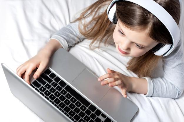 Nettes kleines mädchen mit kopfhörern, das ernsthaft den laptop zu hause für die online-bildung verwendet