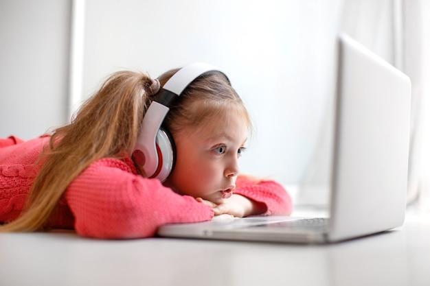 Nettes kleines mädchen mit kopfhörern, das ernsthaft den laptop zu hause für die online-kommunikation verwendet