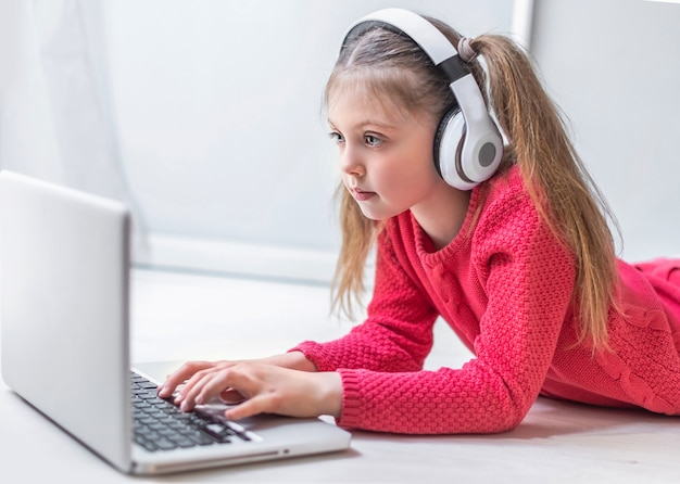 Nettes kleines mädchen mit kopfhörern, das ernsthaft den laptop zu hause für online-bildung und heimstudium verwendet