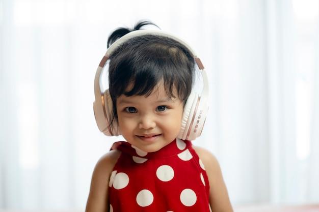Nettes kleines mädchen mit kopfhörern zu hause