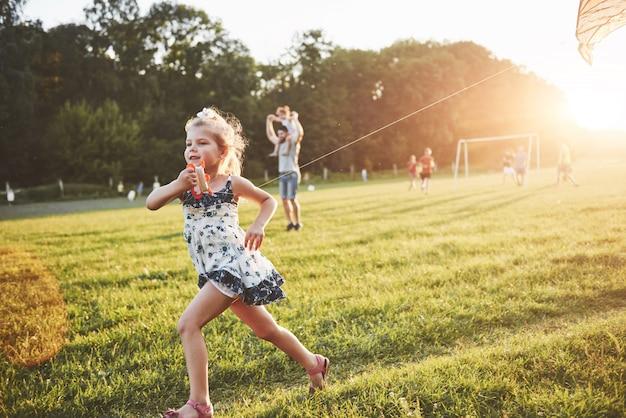 Nettes kleines mädchen mit langen haaren, die mit drachen auf dem feld am sonnigen sommertag laufen