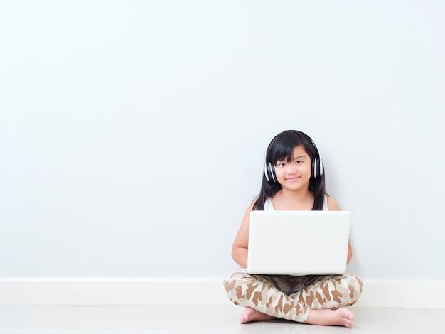 Nettes kleines mädchen mit laptop zu hause