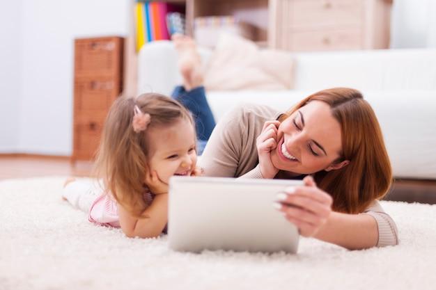 Nettes kleines mädchen mit mutter, die digitales tablett zu hause verwendet