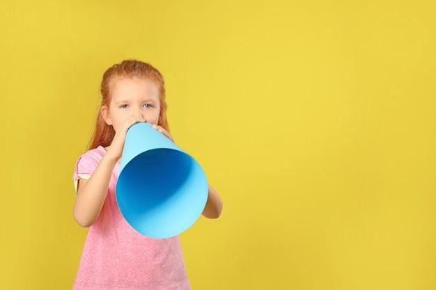 Nettes kleines mädchen mit papiermegaphon auf farbe
