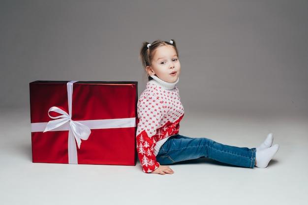 Nettes kleines mädchen mit pferdeschwänzen im winterpullover und in den jeans, die zurück zu rotem eingewickeltem weihnachtsgeschenk mit weißer schleife sitzen. kind schmollt lippen an der kamera.
