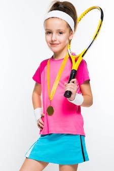 Nettes kleines mädchen mit tennisschläger und medaille in ihren händen