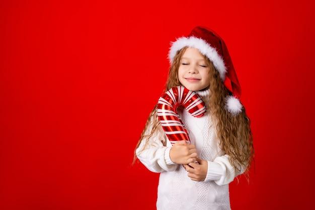 Nettes kleines mädchen mit weihnachtsmannmütze und einem pullover