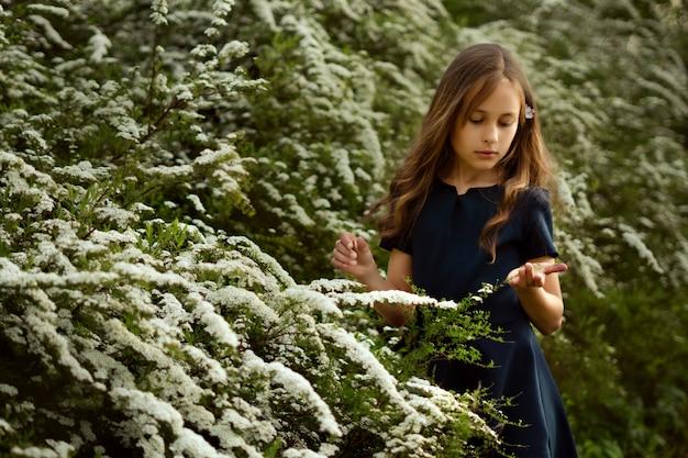 Nettes kleines mädchen nahe schönen weißen blühenden büschen