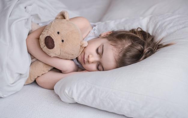 Nettes kleines mädchen schläft süß in einem weißen gemütlichen bett mit einem weichen bärenspielzeug, dem konzept der kinderruhe und des schlafes