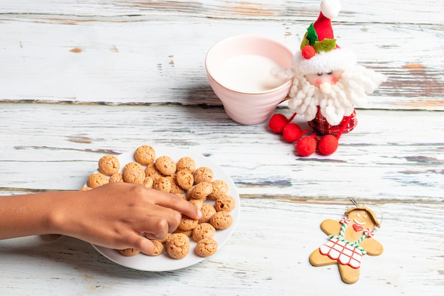 Nettes kleines mädchen spielt mit sankt plätzchen und milch am weihnachten