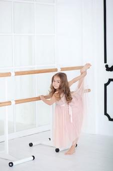 Nettes kleines mädchen träumt davon, eine ballerina zu werden. kindermädchen im rosa kleidertanzen im raum. baby studiert ballett. kleines mädchen, das ein musikalisches spielzeugkarussell hält. drinnen ballettsaal klassenzimmer