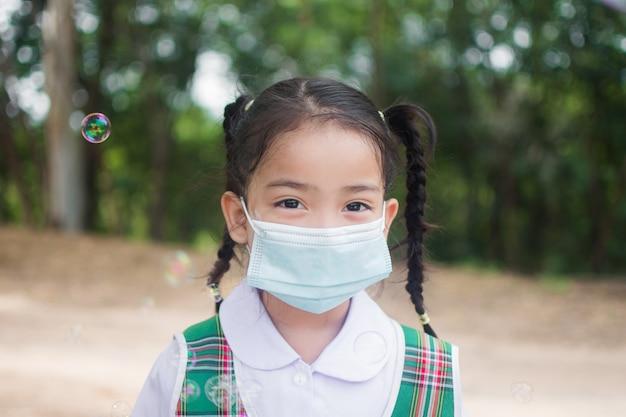 Nettes kleines mädchen tragen maske zum schutz coronavirus oder covid 19.