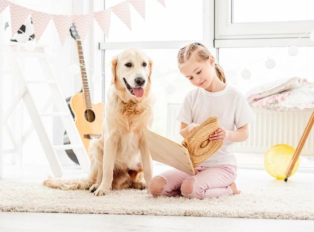 Nettes kleines mädchen und hund lesen