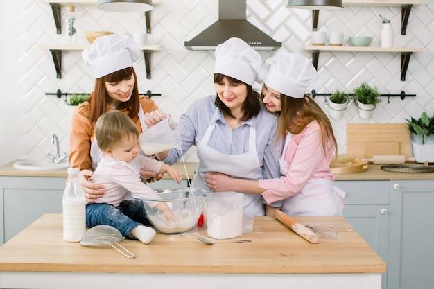 Nettes kleines mädchen und ihre schöne mutter, tante und großmutter in schürzen und hüten, die spaß haben, während sie milch zu mehl gießen und den teig in der modernen küche bei sweet home kneten. frauen backen in der küche