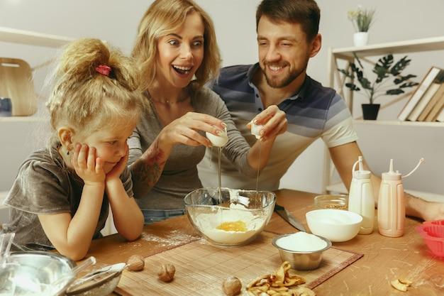 Nettes kleines mädchen und ihre schönen eltern bereiten den teig für den kuchen in der küche zu hause vor. familienlebensstilkonzept