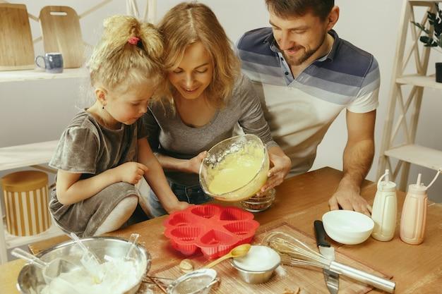 Nettes kleines mädchen und ihre schönen eltern bereiten den teig für den kuchen in der küche zu hause vor