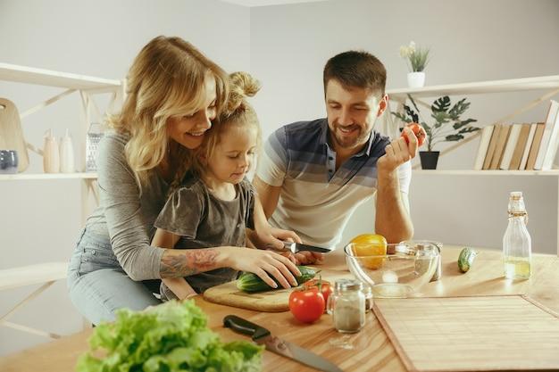 Nettes kleines mädchen und ihre schönen eltern schneiden gemüse und lächeln, während sie salat in der küche zu hause machen. familienlebensstilkonzept