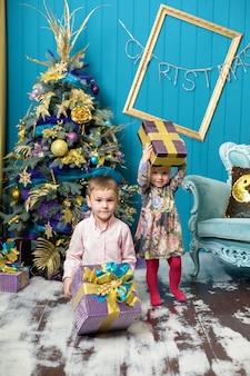 Nettes kleines mädchen und junge lächeln und halten geschenke unter dem weihnachtsbaum.