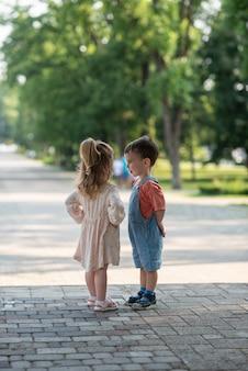 Nettes kleines mädchen und junge stehen unter einem baum und umarmen sich
