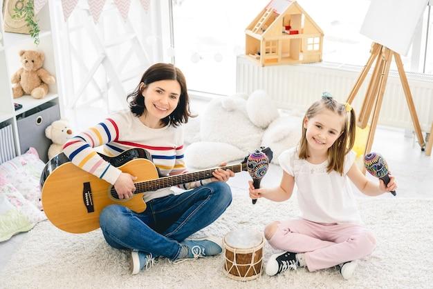 Nettes kleines mädchen und mutter, die musikinstrumente im kinderzimmer spielen?