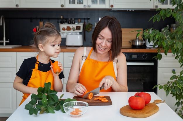 Nettes kleines mädchen und schöne mutter in der orangefarbenen schürze kochen, schneiden, hacken gemüse, lächeln, haben spaß am küchenhintergrund, kopieren raum