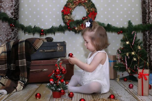 Nettes kleines mädchen verkleidet weihnachtsbaum auf dem boden im zimmer