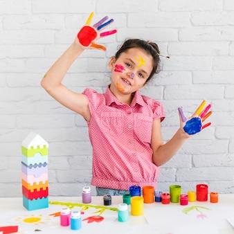 Nettes kleines mädchen, welches die gemalten hände steht vor tabelle mit bunten farben zeigt