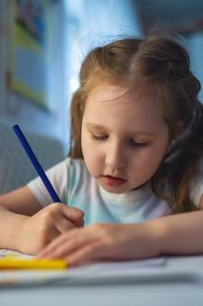 Nettes kleines mädchen zeichnet ein bild mit buntstiften