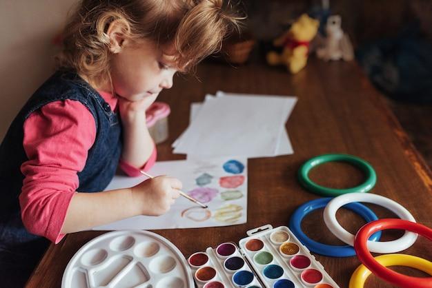 Nettes kleines mädchen zeichnet einen kreis von farbigen farben