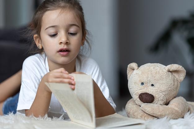 Nettes kleines mädchen zu hause, das mit ihrem lieblingsspielzeug auf dem boden liegt und ein buch liest.