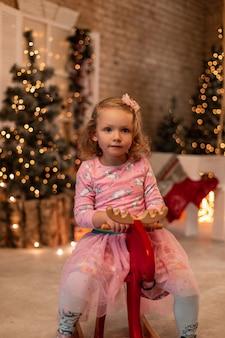 Nettes kleines mädchenkind in einem modischen rosa kleid sitzt auf einem roten spielzeugelch